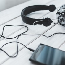 A photo showing a smartphone with connected headphones